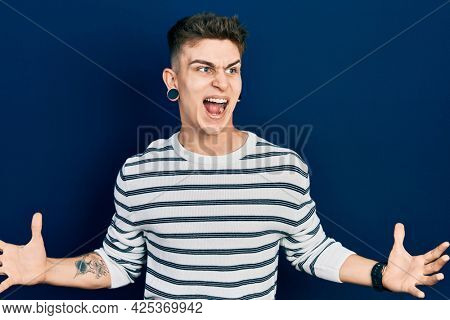 Young caucasian boy with ears dilation wearing casual striped shirt crazy and mad shouting and yelling with aggressive expression and arms raised. frustration concept.