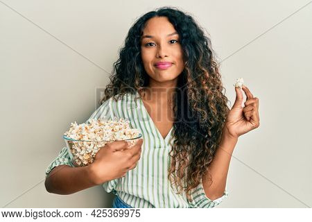 Young latin woman eating popcorn relaxed with serious expression on face. simple and natural looking at the camera.
