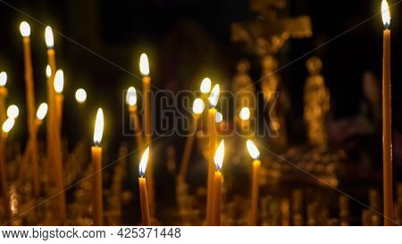 Close-up Of Burning Wax Candles Against The Background Of A Blurred Crucifix In A Christian Temple.