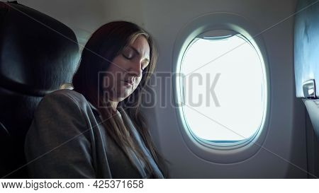 Brunette Woman Sleeping While Sitting In An Uncomfortable Position On The Plane.