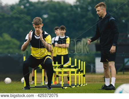 Group Of Football Players On Agility Training. Young Coach Giving Advices To Player On Training. Coa