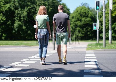 Man And Woman Cross The Road At Pedestrian Crossing