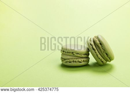 Pistachio flavor French macaron cookies on background of the same pastel green colour with copy space