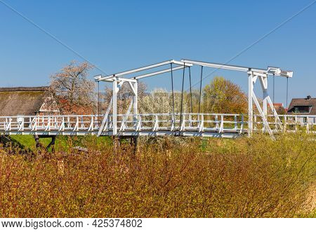 Wooden drawbridge across Lühe river at Altes Land region of Lower Saxony, farmhouse with blooming apple and cherry in background