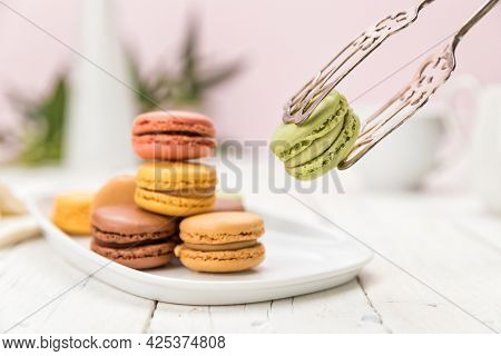Assortment of French macarons pastry on coffee table, focus on a pistachio flavored one held up with pastry tongs,