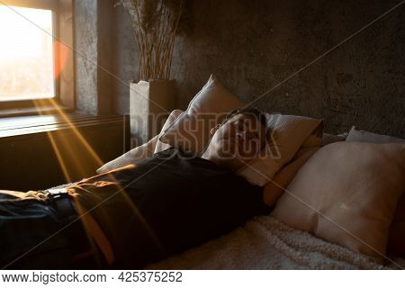 The Man Is Sleeping Peacefully In The Bedroom, Relaxing. A Calm And Peaceful Man Sleeps In Bed.