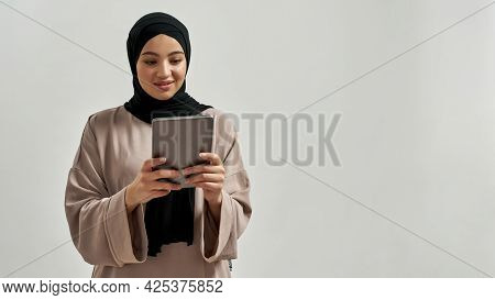 Cute Young Arabic Woman In Hijab Looking Into Digital Tablet Screen While Posing On Light Background