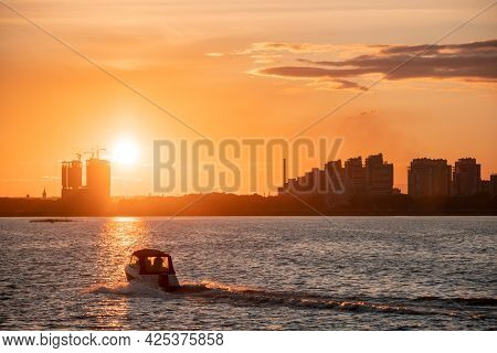 Silhouettes Of City Buildings On The Shore Against The Background Of The Setting Sun And Glare On Th