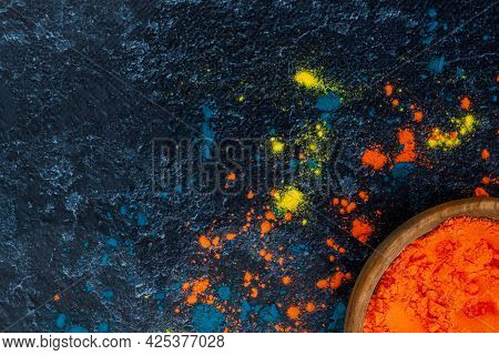 Top View Of Bright Traditional Holi Paints In Wooden Bowl Isolated On Dark Background. Colorful Powd