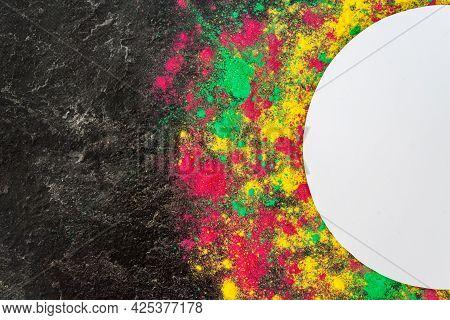 Color Splash Of Holi Powder, Dry Paints Gulal Around Circle Border Isolated On Dark Concrete Backgro