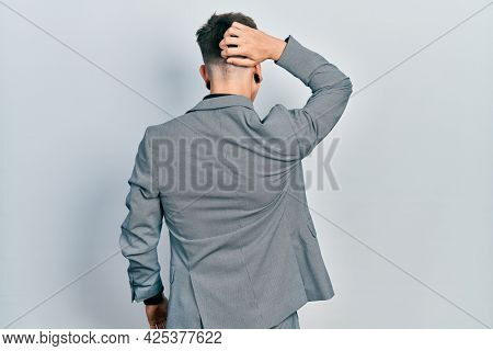 Young caucasian boy with ears dilation wearing business jacket backwards thinking about doubt with hand on head