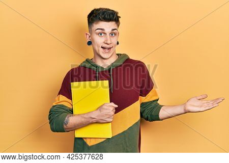 Young caucasian boy with ears dilation holding book celebrating achievement with happy smile and winner expression with raised hand