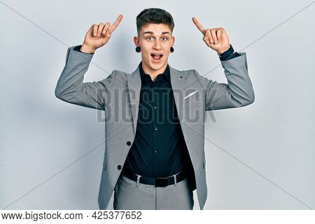 Young caucasian boy with ears dilation wearing business jacket smiling amazed and surprised and pointing up with fingers and raised arms.