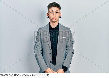 Young caucasian boy with ears dilation wearing business jacket depressed and worry for distress, crying angry and afraid. sad expression.