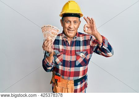 Senior hispanic man wearing handyman uniform holding turkish liras doing ok sign with fingers, smiling friendly gesturing excellent symbol