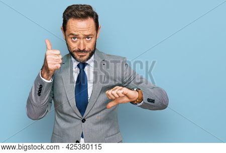 Middle age man wearing business clothes doing thumbs up and down, disagreement and agreement expression. crazy conflict