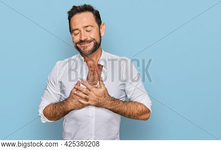 Middle age man wearing casual clothes smiling with hands on chest with closed eyes and grateful gesture on face. health concept.
