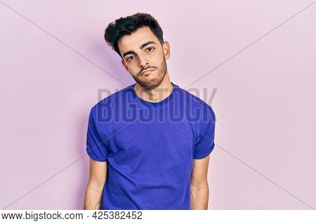 Young hispanic man wearing casual t shirt looking sleepy and tired, exhausted for fatigue and hangover, lazy eyes in the morning.