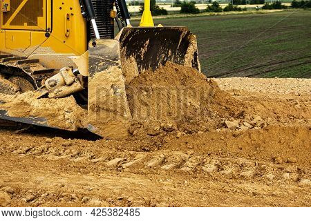 Asphalt Road Construction Process. The Bulldozer Levels And Compacts The Clay Soil For The Base Of T