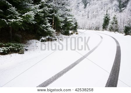 Car tire tracks on the snow, on a mountain road poster