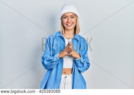 Beautiful blonde woman wearing wool hat hands together and fingers crossed smiling relaxed and cheerful. success and optimistic