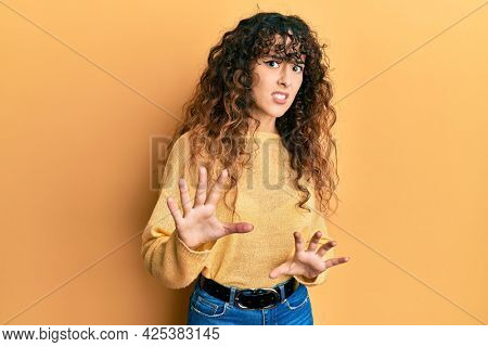 Young hispanic girl wearing casual clothes disgusted expression, displeased and fearful doing disgust face because aversion reaction. with hands raised