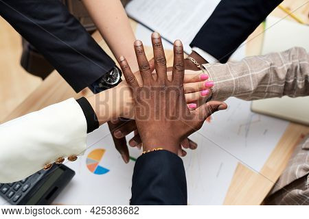 The Black Leaders Hand Covers The Hands Of The Business Team. A Circle From The Hands Of Multiethnic