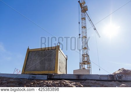 Crane Counterweight Against The Background Of A Construction Crane And Blue Sky. Industrial Tower Cr