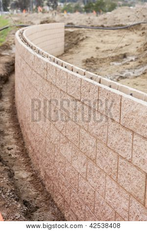 Curved New Outdoor Retaining Wall Being Built at Construction Site.