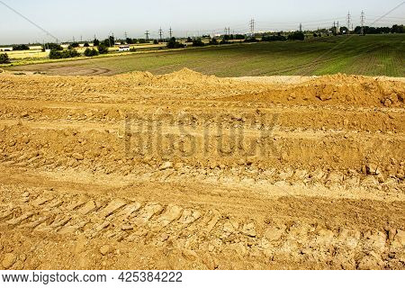 Clay Soil After Leveling With A Bulldozer. Excavator Tracks In Red Mud At A Construction Site.
