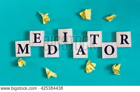 Mediator - Word On Wooden Cubes On A Green Background With Crumpled Yellow Papers. Info Concept