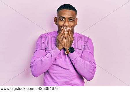 Young black man wearing casual pink sweater laughing and embarrassed giggle covering mouth with hands, gossip and scandal concept