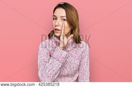 Young caucasian girl wearing wool winter sweater hand on mouth telling secret rumor, whispering malicious talk conversation