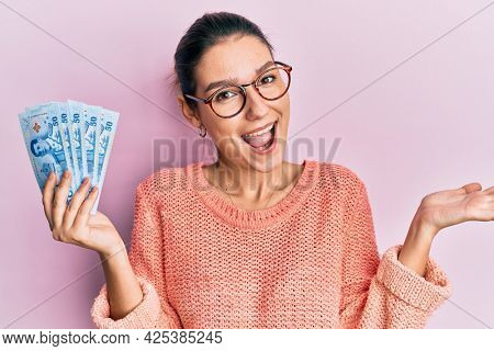 Young caucasian woman holding 50 thai baht banknotes celebrating achievement with happy smile and winner expression with raised hand