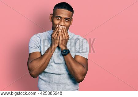 Young black man wearing casual t shirt laughing and embarrassed giggle covering mouth with hands, gossip and scandal concept