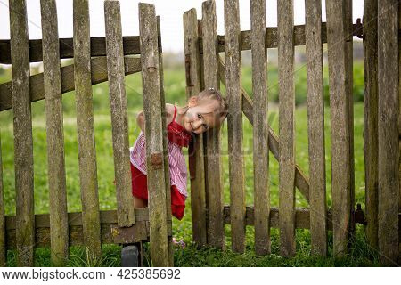 A Little Girl Looks Out From Behind An Old Village Fence With A Gate In The Backyard. A Girl In A Re