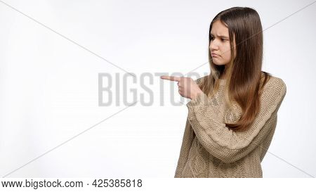 Young Girl Shaking Head And Pointing On Her Side To Show Object. Place Your Product Or Object. Adver