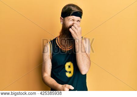 Redhead man with long beard wearing basketball uniform smelling something stinky and disgusting, intolerable smell, holding breath with fingers on nose. bad smell