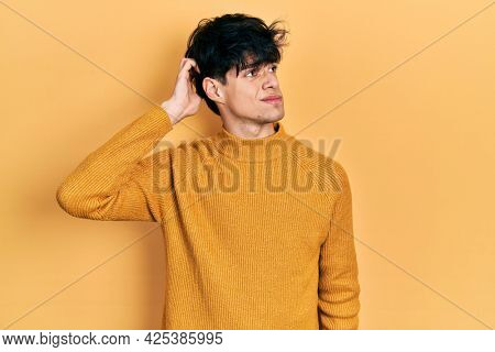 Handsome hipster young man wearing casual yellow sweater confuse and wondering about question. uncertain with doubt, thinking with hand on head. pensive concept.