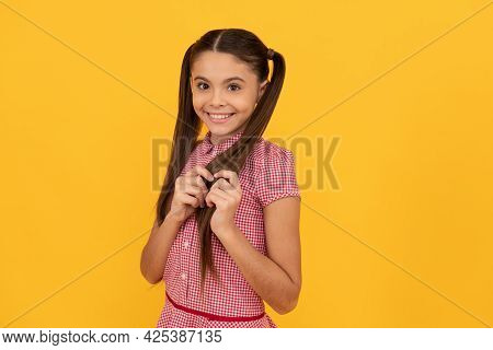 Beautiful Girl Child With Timid Smile Touch Hair Yellow Background, Shy