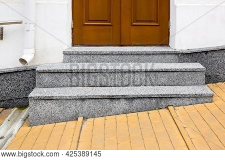 Granite Threshold At The Entrance Door Made Of Brown Wood And White Facade With Stone Cladding Of Bu
