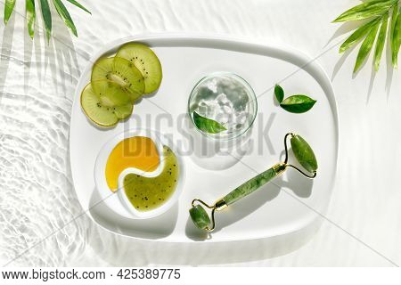 Home Made Cosmetic Wth Kiwi Fruit. Self Made Skincare Background. Jade Stone Face Roller. Anti Aging