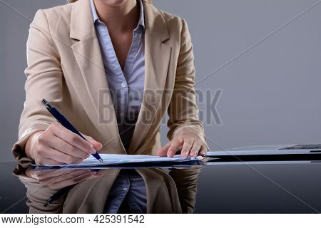 Midsection of caucasian businesswoman using laptop and taking notes, isolated on grey background. business, technology, communication and growth concept.