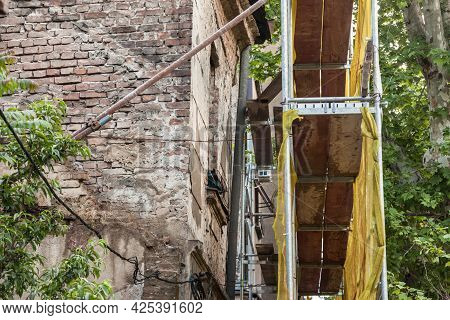 Selective Blur On A Scaffold In Front Of A Facade Of A Damaged Abandoned House Ready To Be Rebuilt,