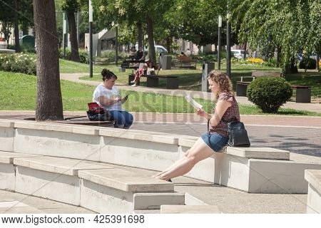 Szeged, Hungary - July 21, 2017: Selective Blur And Contrast Between A Woman Reading A Book And Anot