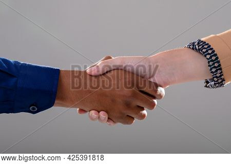 Midsection of caucasian and african american business people shaking hands on grey background. business, technology, communication and growth concept.
