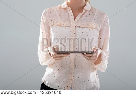 Midsection of caucasian businesswoman using tablet, isolated on grey background. business, technology, communication and growth concept.