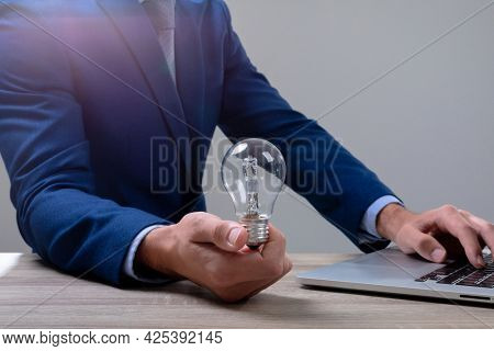 Midsection of caucasian businessman holding light bulb using laptop, isolated on grey background. business technology, communication and growth concept.