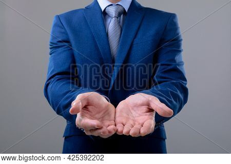Midsection of caucasian businessman showing his hands, isolated on grey background. business technology, communication and growth concept.