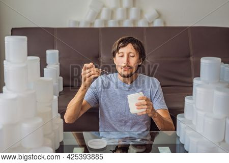 The Man Eats Yogurt And Is Surrounded By Many Jars Of Yoghurt That He Uses In A Year. A Huge Amount